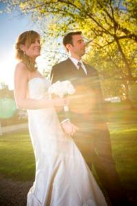 The bride and groom holding hands in the sunlight - Photo by Blue Sky Photography