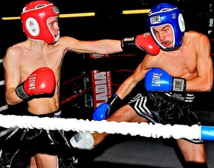 Two men kick boxing in a ring