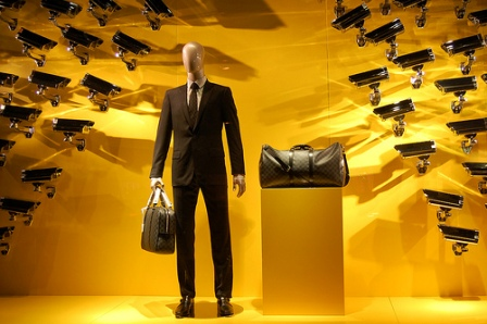 A business man with his suitcases surrounded by televisions