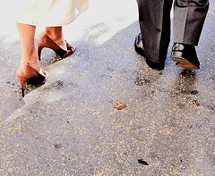 The bride and groom's feet as they walk down the sidewalk side by side