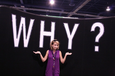 A girl standing in front of the question why